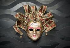 Schöne klassische Maske von Venedig auf schwarzer Wand. Karnevalsmaske Lizenzfreies Stockfoto