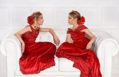 Schöne kleine Mädchen in den roten Kleidern Stockbilder