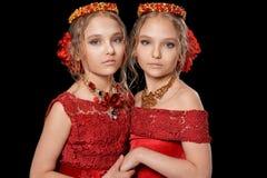 Schöne kleine Mädchen in den roten Kleidern Stockfotografie