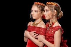 Schöne kleine Mädchen in den roten Kleidern Stockfotos