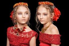 Schöne kleine Mädchen in den roten Kleidern Stockbild