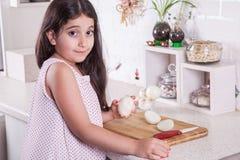 Schöne kleine nahöstliche 7 Jahre alte Mädchen arbeitet mit Messer und Zwiebel in der weißen Küche Schönes Tanzen der jungen Frau Stockfoto