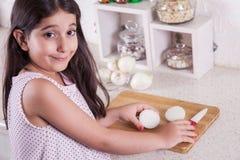 Schöne kleine nahöstliche 7 Jahre alte Mädchen arbeitet mit Messer und Zwiebel in der weißen Küche Schönes Tanzen der jungen Frau Stockbild