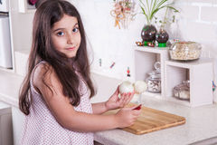 Schöne kleine nahöstliche 7 Jahre alte Mädchen arbeitet mit Messer und Zwiebel in der weißen Küche Schönes Tanzen der jungen Frau Stockbilder