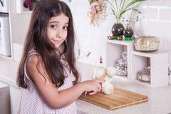 Schöne kleine nahöstliche 7 Jahre alte Mädchen arbeitet mit Messer und Zwiebel in der weißen Küche Schönes Tanzen der jungen Frau Lizenzfreies Stockfoto