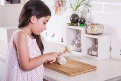 Schöne kleine nahöstliche 7 Jahre alte Mädchen arbeitet mit Messer und Zwiebel in der weißen Küche Schönes Tanzen der jungen Frau Stockfotos