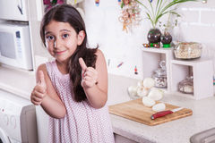 Schöne kleine nahöstliche 7 Jahre alte Mädchen arbeitet mit Messer und Zwiebel in der weißen Küche Schönes Tanzen der jungen Frau Lizenzfreie Stockbilder