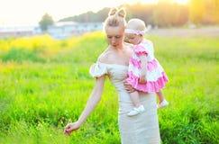 Schöne kleine Tochter der Mutter und des Babys, die ein Kleid trägt Lizenzfreie Stockfotos
