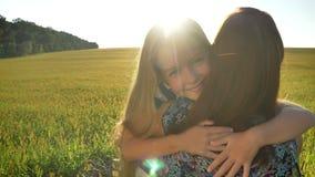 Schöne kleine Tochter mit dem langen blonden Haar, das läuft, um zu bemuttern und herein sie, Weizenfeld während des Sonnenunterg stock video