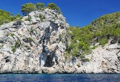 Schöne Klippe im Mittelmeer bedeckt mit grünen Bäumen Hintergrund des blauen Himmels spanien Stockbild