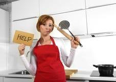 Schöne Kochfrau im verärgerten Umkippen und frustrierten im Gesichtsausdruck, die rotes Schutzblech bitten um die Hilfe hält Nude stockfotografie