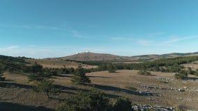 Schöne Koniferenbäume mit grünen Hügeln gegen blauen Himmel und Wolken schuß Ansicht über einen Hügel mit futuristischen Gebäuden stock video footage
