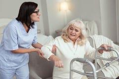 Schöne Krankenschwester, die Bein der älteren Frau aufgibt lizenzfreies stockfoto