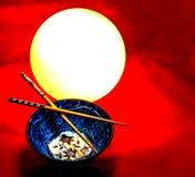 Schöne Kunst mit Porzellanschüssel, Essstäbchen, eine Lampe auf einem roten bewölkten Hintergrund lizenzfreie stockbilder