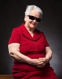 Schöne lächelnde alte Frau in der Sonnenbrille Stockfotos