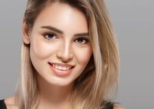 Schöne lächelnde Aufstellung der jungen Frau mit dem blonden Haar auf grauem Hintergrund Stockbild