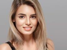 Schöne lächelnde Aufstellung der jungen Frau mit dem blonden Haar auf grauem Hintergrund Lizenzfreies Stockbild