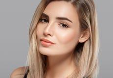Schöne lächelnde Aufstellung der jungen Frau mit dem blonden Haar auf grauem Hintergrund Lizenzfreie Stockfotos