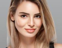 Schöne lächelnde Aufstellung der jungen Frau mit dem blonden Haar auf grauem Hintergrund Lizenzfreies Stockfoto
