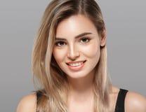 Schöne lächelnde Aufstellung der jungen Frau mit dem blonden Haar auf grauem Hintergrund Stockfotos