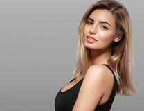 Schöne lächelnde Aufstellung der jungen Frau mit dem blonden Haar auf grauem Hintergrund Lizenzfreie Stockfotografie
