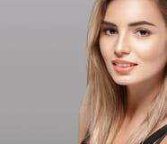 Schöne lächelnde Aufstellung der jungen Frau mit dem blonden Haar auf grauem Hintergrund Stockfotografie