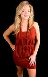 Schöne lächelnde blonde Dame in einem roten Kleid Stockfotografie
