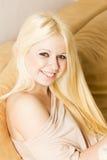 Schöne lächelnde blonde Frau auf dem Bett Stockfotografie