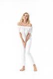 Schöne lächelnde blonde Frau in der weißen Bluse und in den Hosen auf weißem Hintergrund Lizenzfreies Stockbild