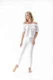Schöne lächelnde blonde Frau in der weißen Bluse und in den Hosen auf weißem Hintergrund Stockbild