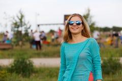 Schöne lächelnde blonde Frau in der zufälligen Art, die auf Natur stillsteht Lizenzfreie Stockfotos