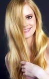 Schöne lächelnde blonde Frau, die ihr Haar bürstend sich pflegt Stockfotos