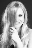 Schöne lächelnde blonde Frau, die ihr Haar bürstend sich pflegt Lizenzfreie Stockfotos