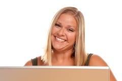 Schöne lächelnde blonde Frau, die Laptop verwendet Stockbilder