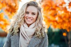 Schöne lächelnde blonde Frau mit dem gelockten Haar und den blauen Augen Lizenzfreies Stockbild