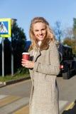 Schöne lächelnde blonde Frau mit dem Kaffee, der die Straße kreuzt Stockfoto