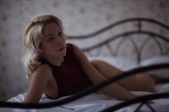 Schöne lächelnde blonde Frau mit den langen dünnen Beinen, die Schlafzimmer aufwerfen Stockfoto