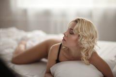 Schöne lächelnde blonde Frau mit den langen dünnen Beinen, die Schlafzimmer aufwerfen Stockfotos