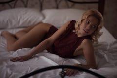 Schöne lächelnde blonde Frau mit den langen dünnen Beinen, die Schlafzimmer aufwerfen Stockfotografie