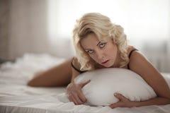 Schöne lächelnde blonde Frau mit den langen dünnen Beinen, die Schlafzimmer aufwerfen Lizenzfreie Stockbilder