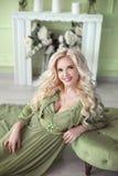 Schöne lächelnde blonde Frau mit langer gelockter Frisur trägt i Lizenzfreies Stockfoto