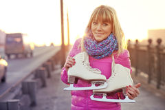 Schöne lächelnde blonde Frau mit Schlittschuhen Stockbilder