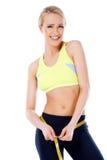 Schöne lächelnde blonde sportliche Frau, die ihre Taille misst Stockfotos