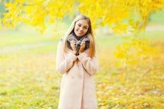 Schöne lächelnde Blondine des Porträts im warmen sonnigen Herbst Lizenzfreies Stockfoto