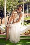 Schöne lächelnde Braut im eleganten Hochzeitskleid, das im Garten aufwirft Stockbilder