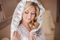 Schöne lächelnde Braut im Hochzeitsschleier Getrennt auf Weiß glücklich lizenzfreie stockfotos
