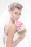 Schöne lächelnde Braut im Schleier mit Blumenstrauß Lizenzfreies Stockfoto