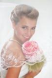 Schöne lächelnde Braut im Schleier mit Blumenstrauß Stockfoto