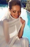 Schöne lächelnde Braut mit dem blonden Haar im eleganten Hochzeitskleid Lizenzfreies Stockbild