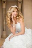 Schöne lächelnde Brautfrau mit dem langen gelockten Haar, das herein aufwirft, heiraten Lizenzfreie Stockbilder